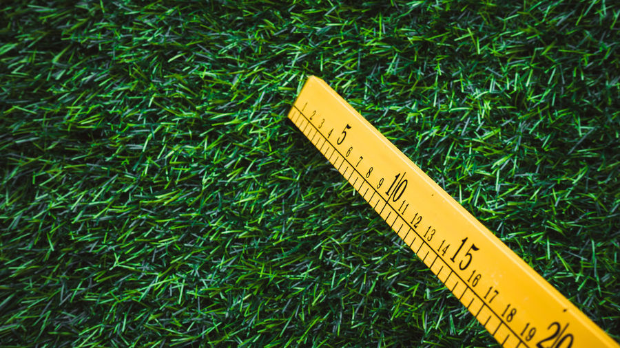 Close-up of measuring tape on grass field