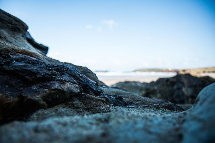 Surface level of rocky shore against clear sky
