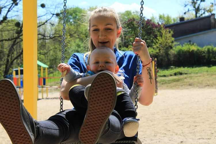 Portrait of mother and son playing on swing