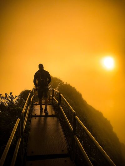 Man walking on mountain against orange sky