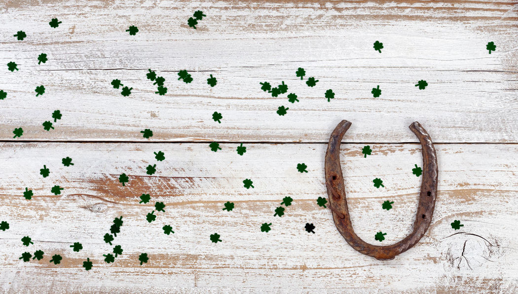 St Patrick day good luck horseshoe with shiny clovers on rustic white wooden boards in overhead view Clover Holiday Luck St Patrick's Day Backgrounds Horsehorse Irish St Patrick Studio Shot Wood - Material