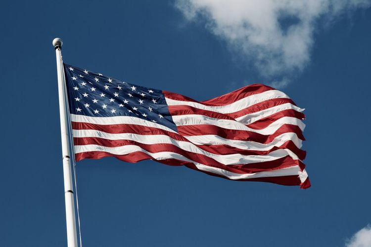 Low angle view of the us flag against blue sky