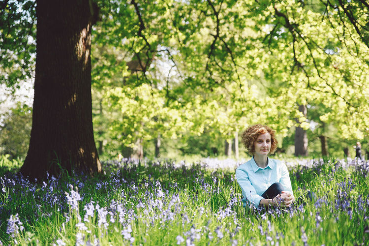 Thoughtful Young Woman Sitting Amidst Plants In Forest On Sunny Day