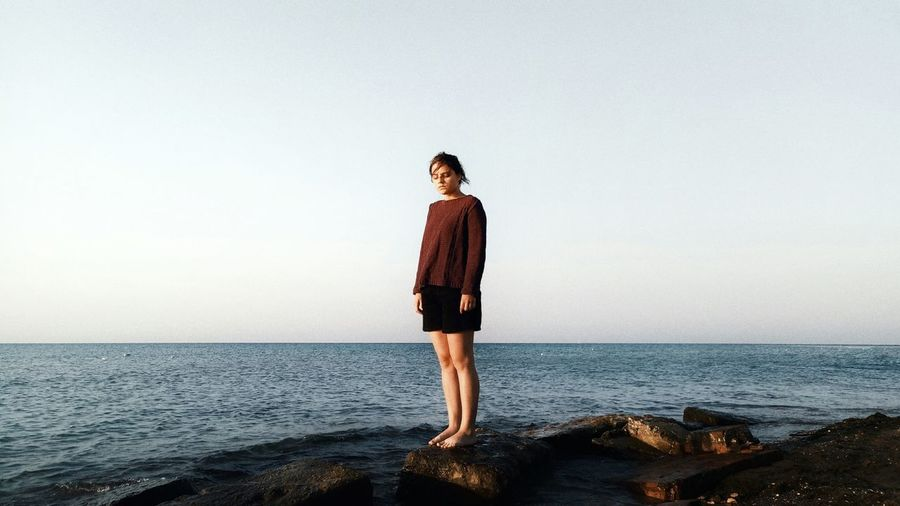 Young Woman Standing In Front Of Sea Against Clear Sky