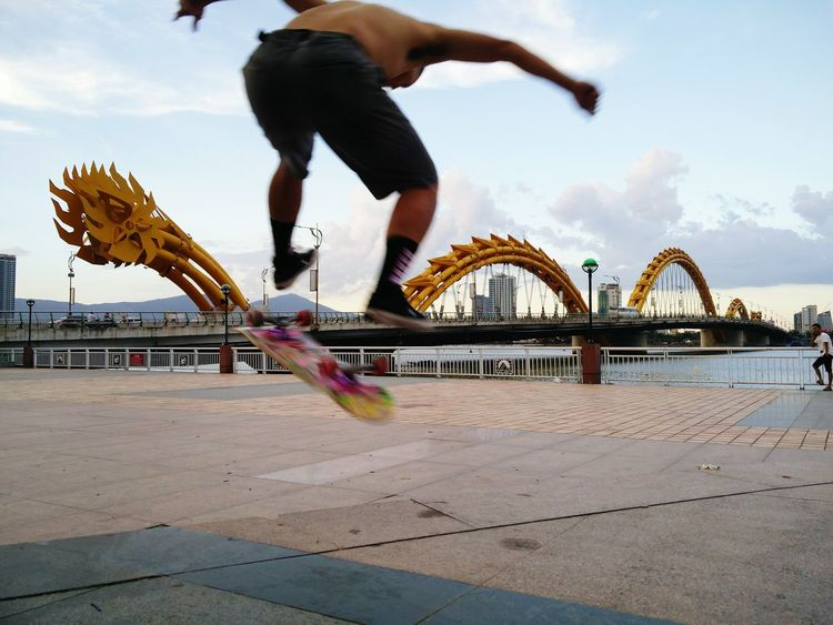 Scate boarding besides Dragon Bridge and in front of Museum of Sculptures in Danang, central Vietnam, summer time sporting. Injuries do not intimidate, falls don't shame, persistence pays. #Summer Sports #dragon Bridge #da Nang #Vietnam #Practice #persistence #photography #travelphotography #cityscapes #citylights #activelife #Challenger #flyingbirds #streetphotography #streetlife #boy #young #youth #architecture #HanRiver #Delta City Sport Men Motion Activity Athlete Extreme Sports Skill  Competition