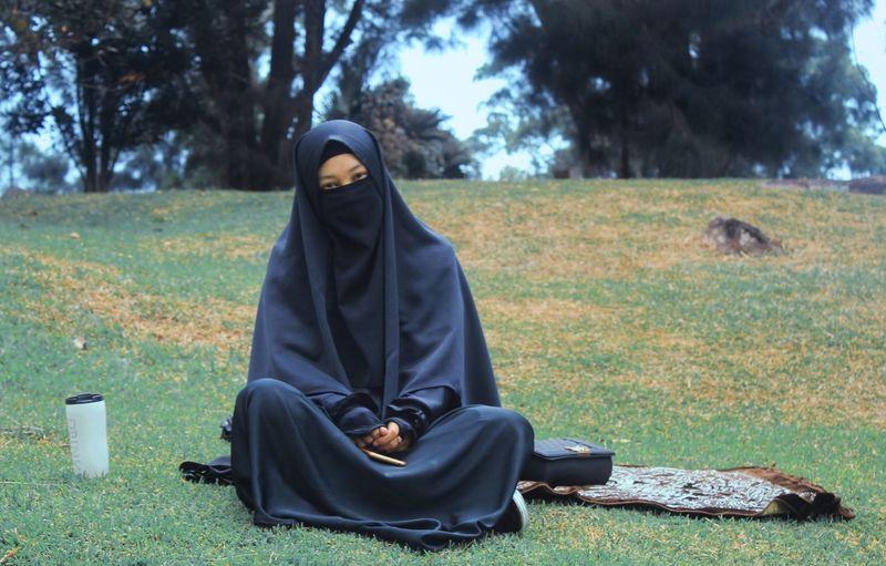 Portrait of woman in burka sitting on field