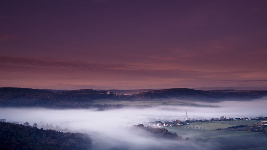 Scenic view of foggy landscape against sky at night