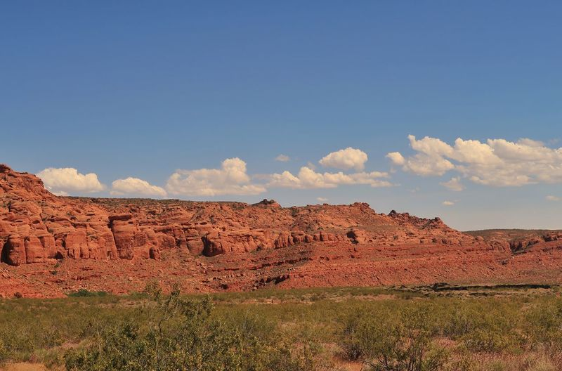 Landscape of red rock hill and grassy area in Snow Canyon State Park in Utah Red Rock Utah Snow Canyon State Park EyeEm Selects Sky Landscape Nature Cloud - Sky Day No People Tranquility Tranquil Scene Blue Field Plant Rural Scene Outdoors Land Scenics - Nature Environment Sunlight