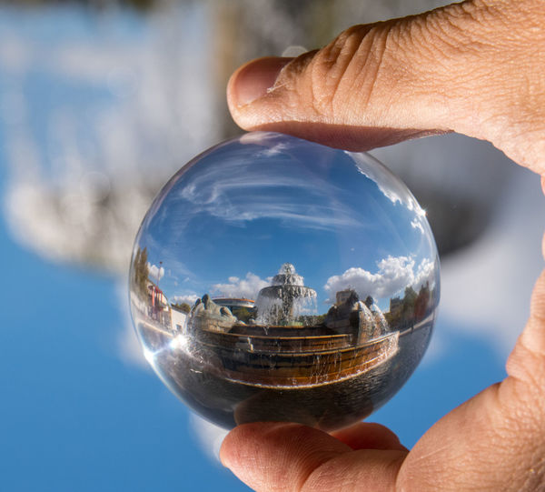 Cropped hand holding crystal ball against historic building