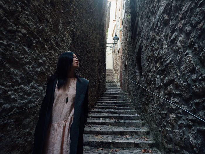 Woman standing on staircase by wall