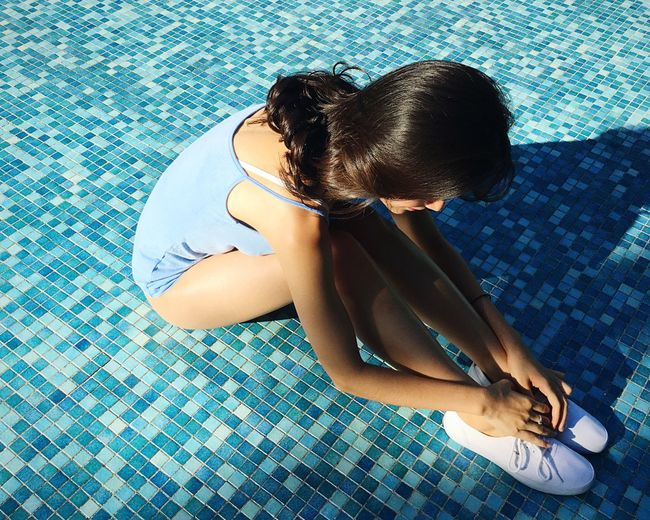 High angle view of young woman sitting on swimming pool