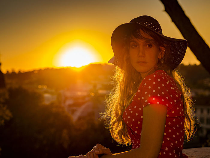 Woman Wearing Hat Standing Against Sky During Sunset