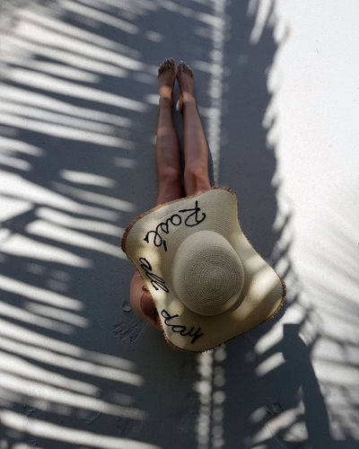 Directly above shot of woman wearing hat with text while sitting at beach