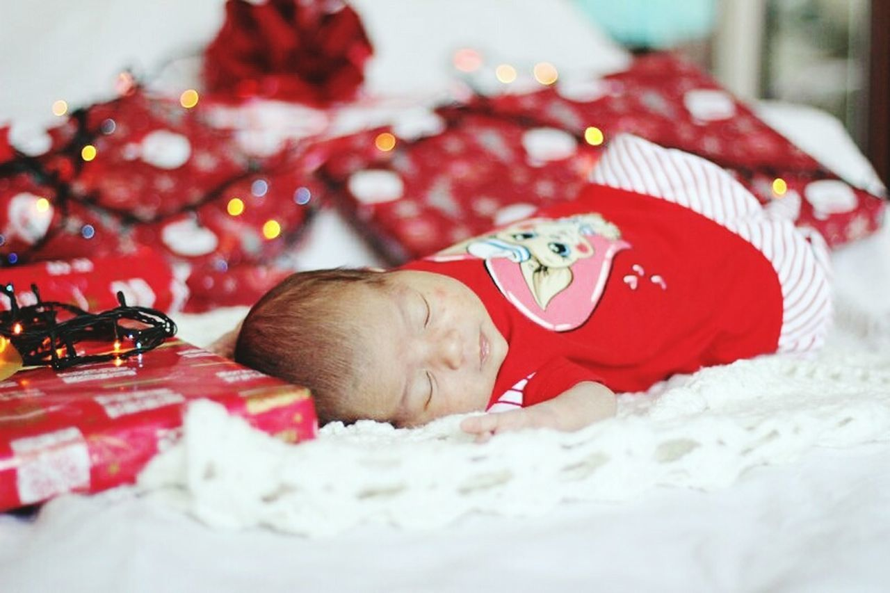 baby, indoors, babyhood, selective focus, lying down, red, real people, one person, bed, home interior, christmas, fragility, close-up, babies only, day, animal themes, people