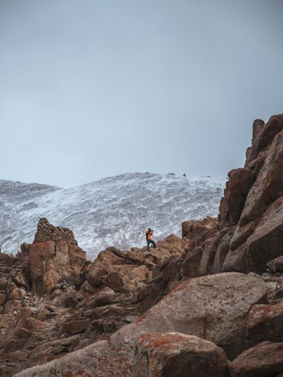 Mid distance of male hiker standing on rocky mountain against clear sky