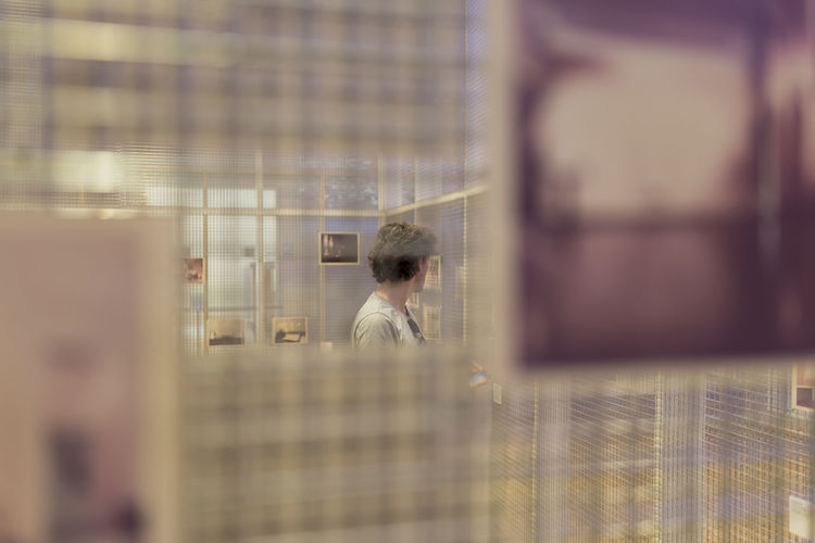 Portrait of man looking through display grid