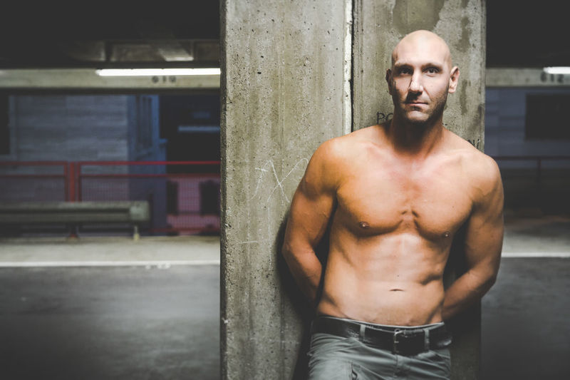 Shirtless muscular man leaning on wall in parking lot