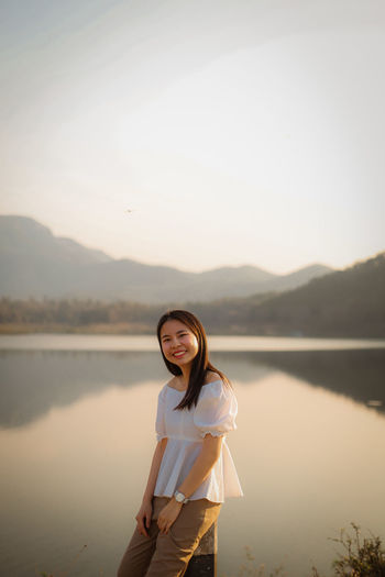 Portrait of young woman standing in lake against sky