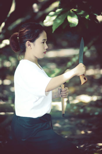Side view of woman holding knife practicing martial arts outdoors