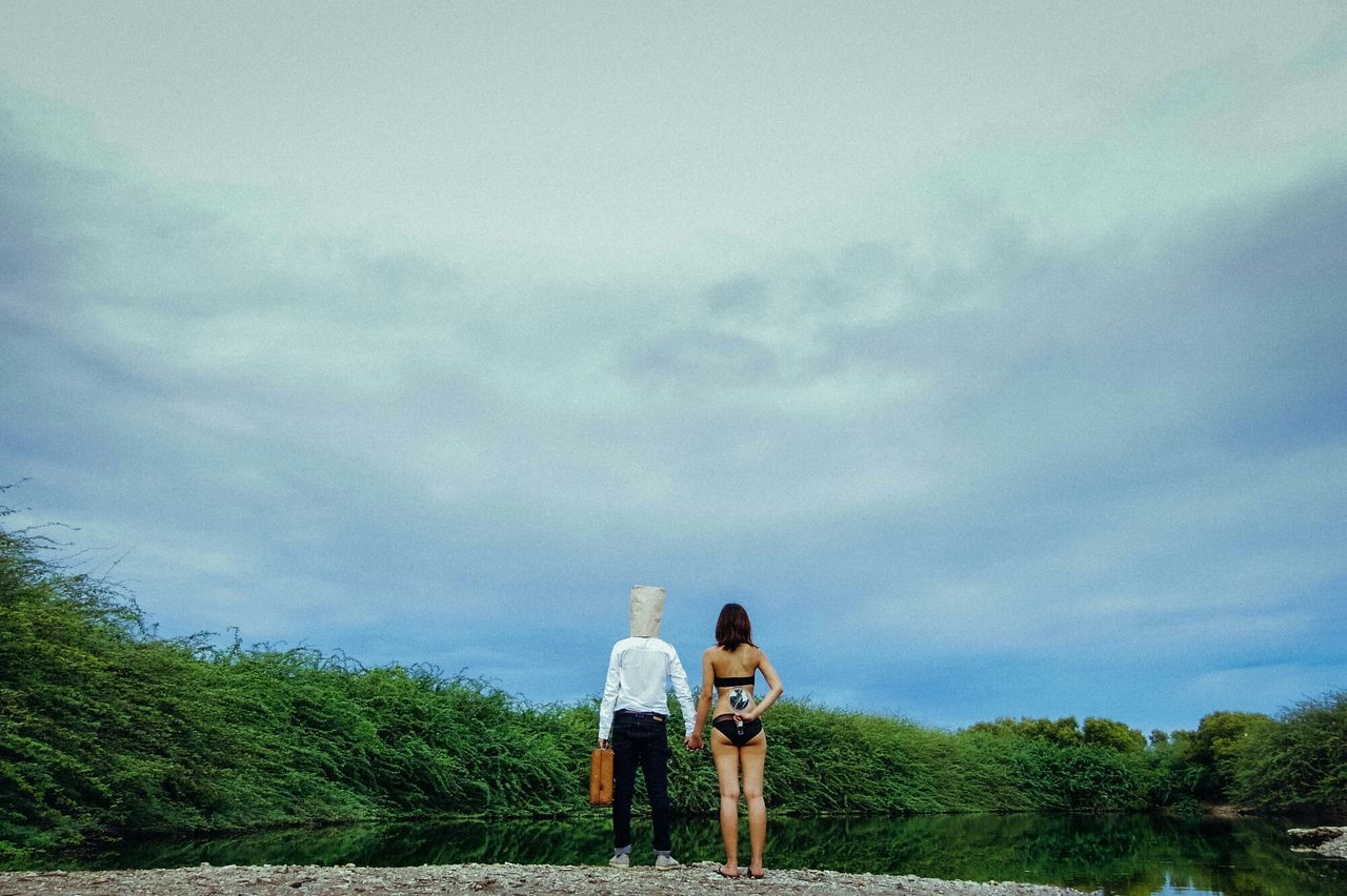 Rear view of couple standing on lakeshore against cloudy sky