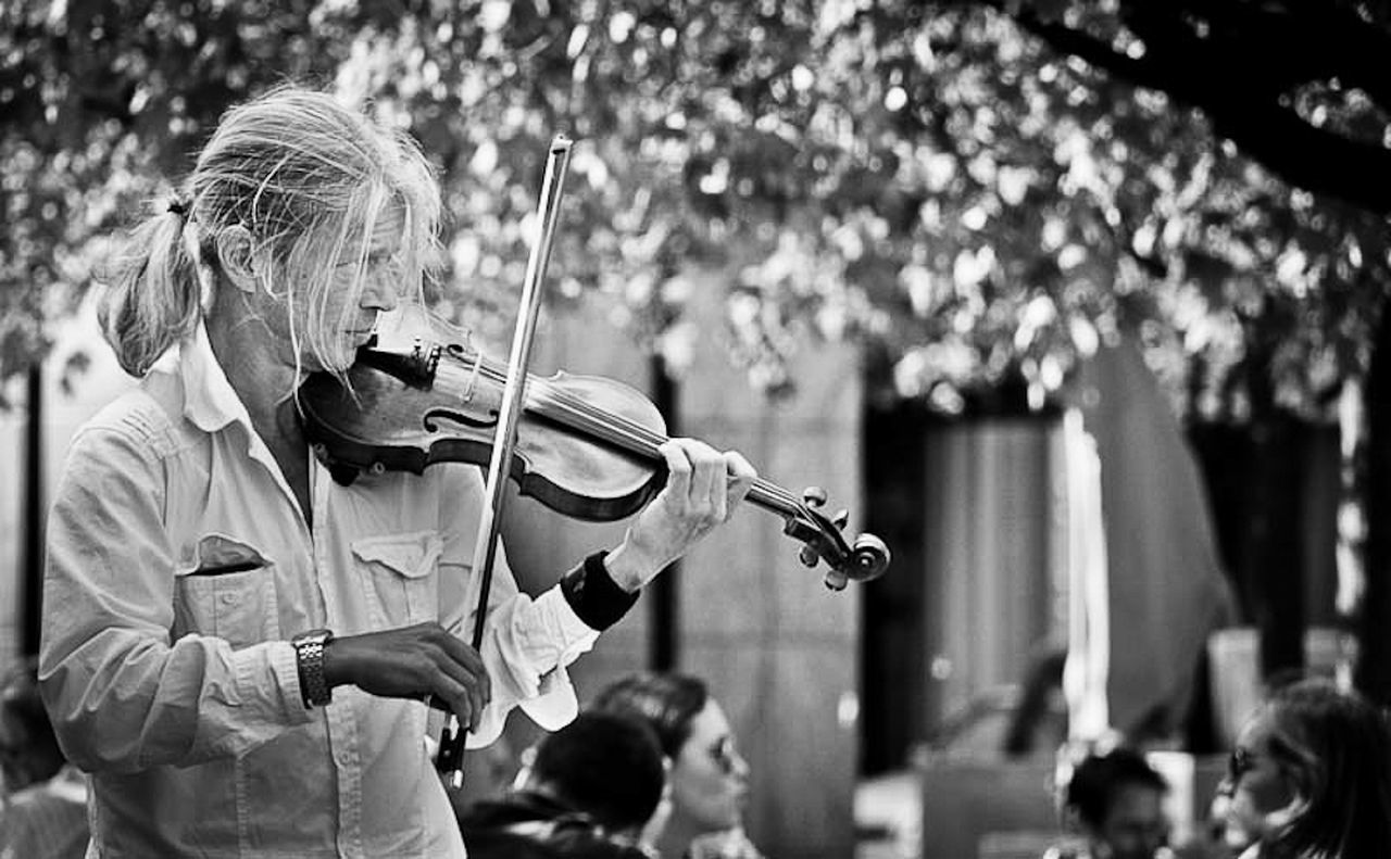 real people, focus on foreground, incidental people, people, playing, waist up, music, holding, musical instrument, arts culture and entertainment, day, standing, musician, performance, crowd, adult, artist, outdoors, men, obscured face