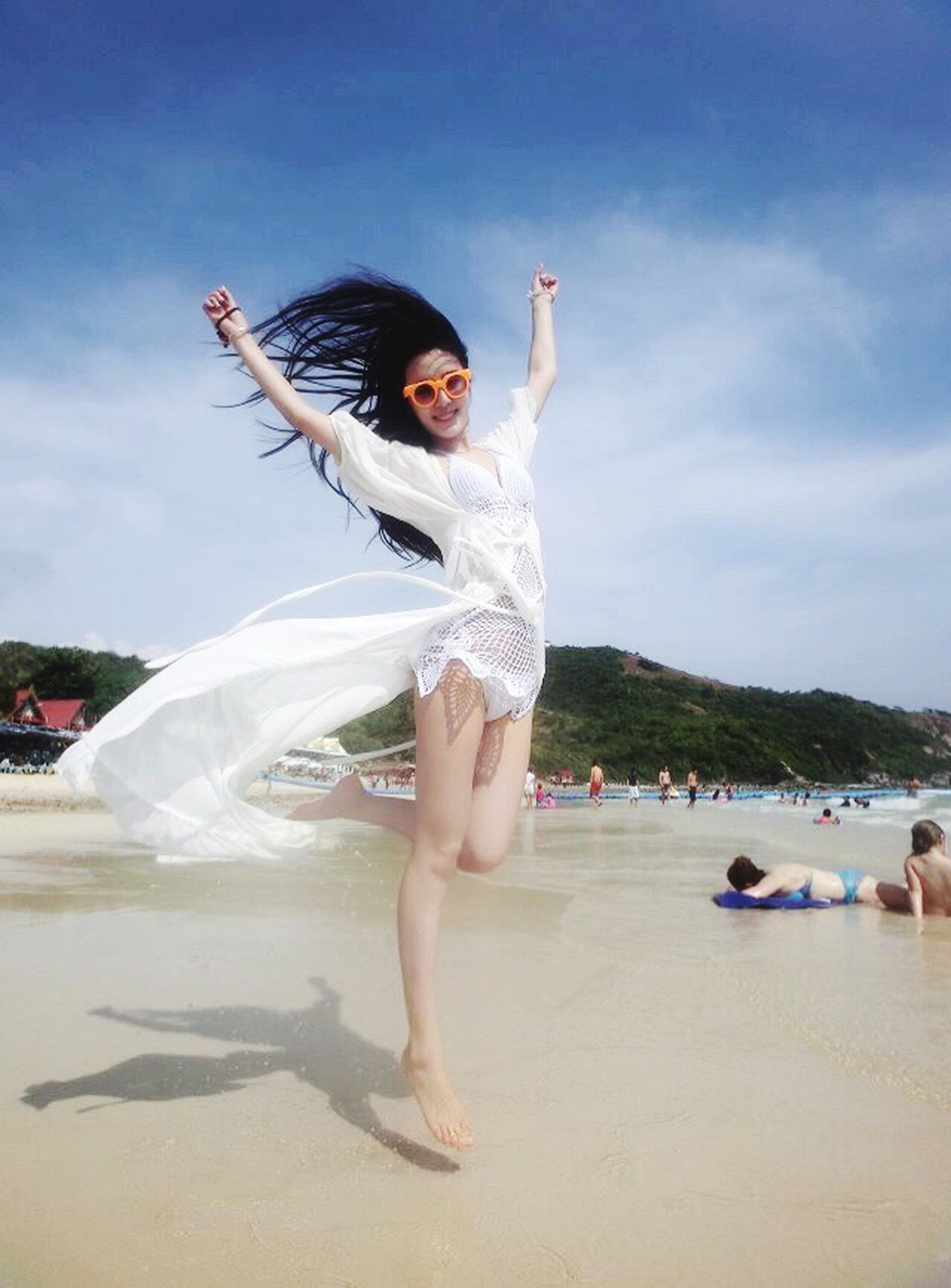 full length, lifestyles, person, leisure activity, young adult, enjoyment, happiness, fun, casual clothing, arms outstretched, mid-air, young women, arms raised, front view, sky, jumping, childhood, carefree
