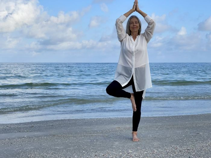 Senior woman relaxing in a standing  yoga  pose on the beach with the sea and sky as background