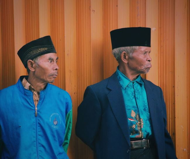 Mature men looking away while wearing traditional caps