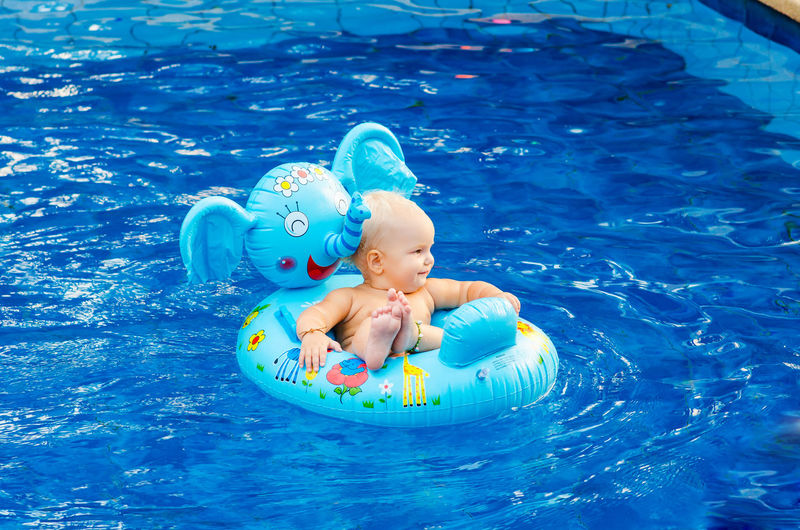 High angle view of shirtless girl sitting in inflatable ring on swimming pool
