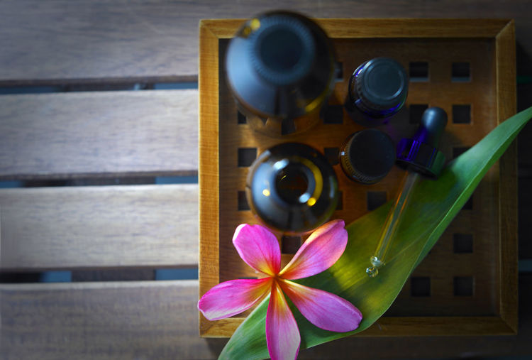Bottles of aromatherapy oil and flower Frangipani Tray Wellness Close-up Day Essential Oils Flower Flower Head Freshness Indoors  Liftstyle Massage Oil Nature No People Pipette Spa Treatment Table Top View Treatment Wellbeing Wood - Material