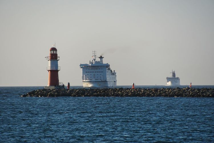 Lighthouse on pier with cruise ships in sea against clear sky