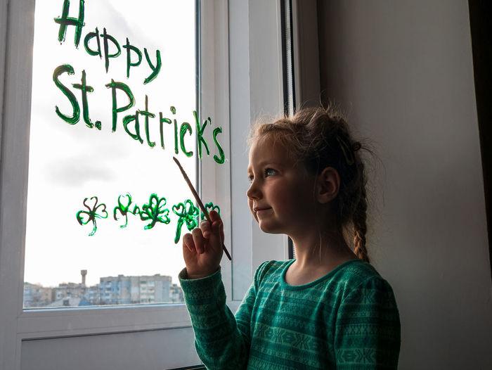Cute girl writing on window at home
