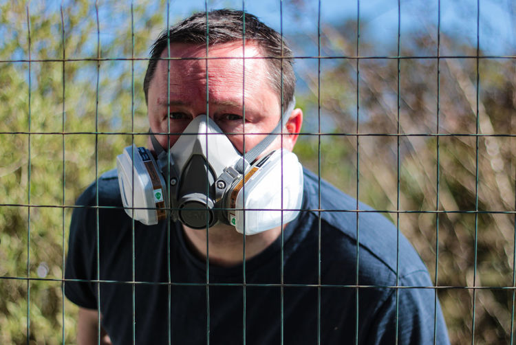 Portrait of man wearing mask seen through fence