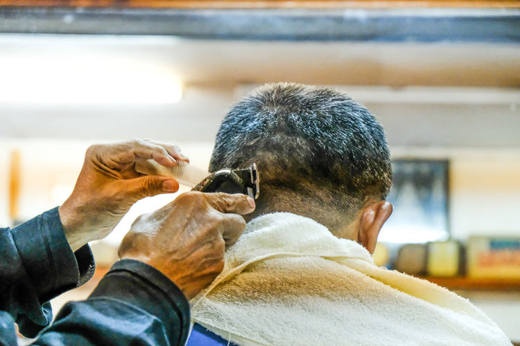 Cropped hands of barber cutting male customer hair in shop