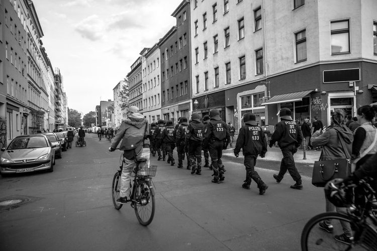 Crowd walking on street amidst buildings at may day