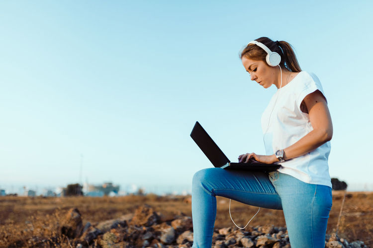 Young woman wearing headphones while using laptop against sky