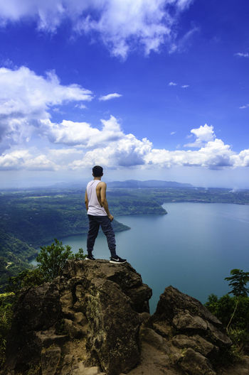 Rear view of man standing on rock over lake against sky