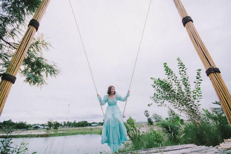 Full length of woman sitting on swing against sky