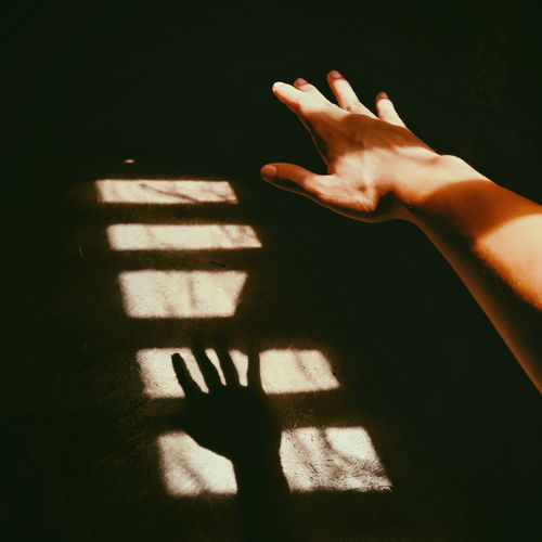 Cropped image of hand with shadow on wall
