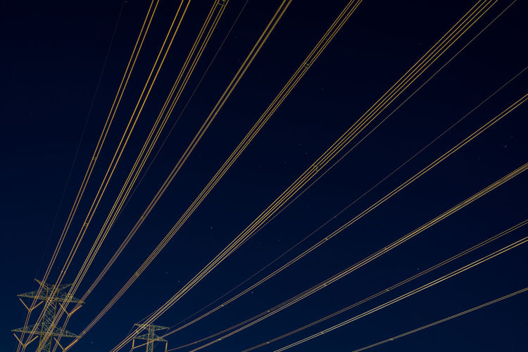 Low angle view of illuminated cables against sky at night