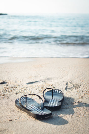 Travel on the island sea the beach Waves and fishing boats Beach Beauty In Nature Day Flip-flop Focus On Foreground Horizon Horizon Over Water Jewelry Land Motion Nature No People Outdoors Personal Accessory Sand Sandal Scenics - Nature Sea Sky Slipper  Water Wave
