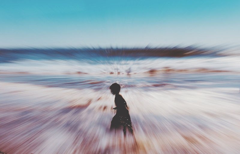 Rear view of woman on sea shore against sky