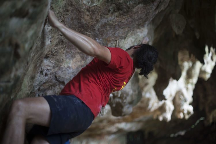 Close-up of person with arms outstretched on rock
