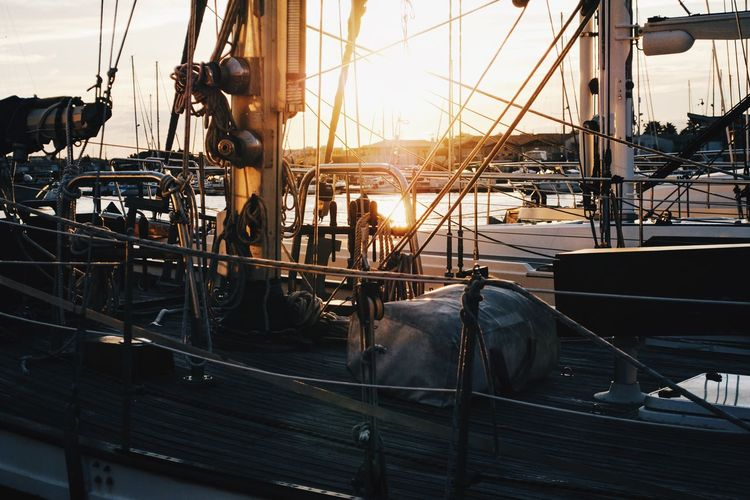 Boat moored at harbor during sunset