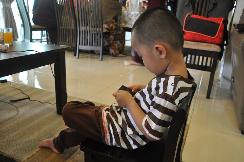 Boy using mobile phone while sitting in home