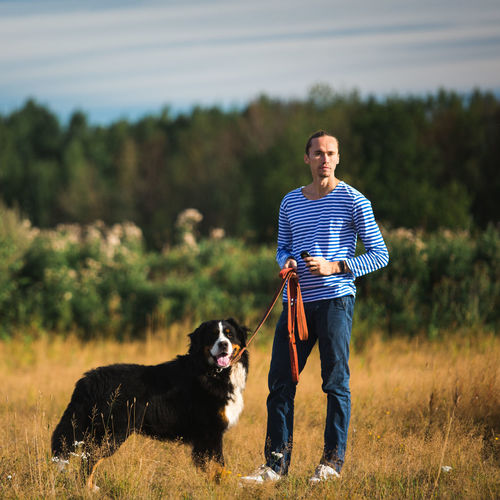 Man with dog standing on land