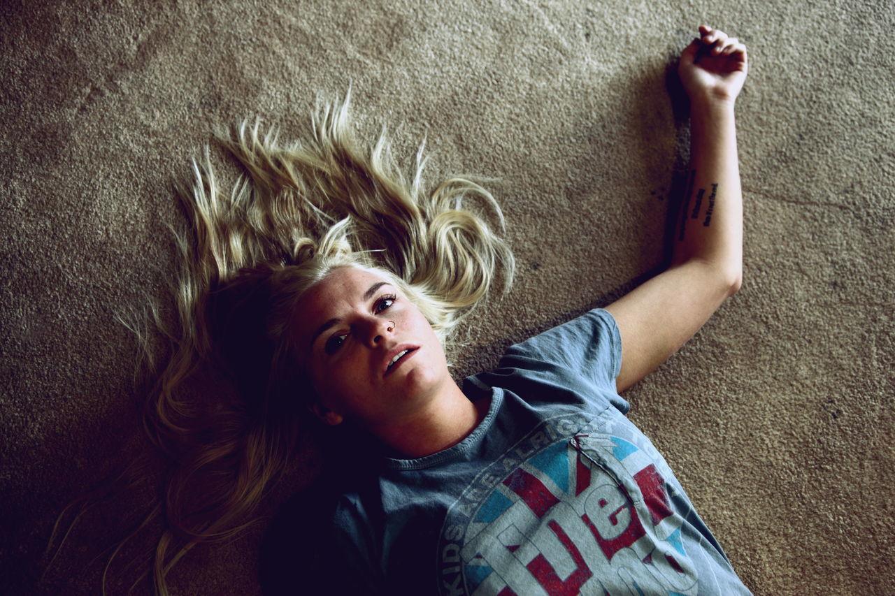 High angle view of sad young woman lying on floor