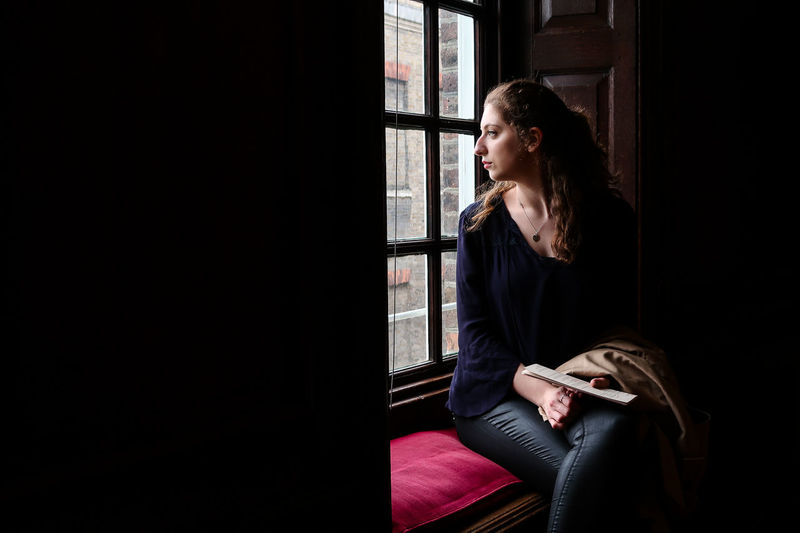 Thoughtful young woman sitting on window seat at home