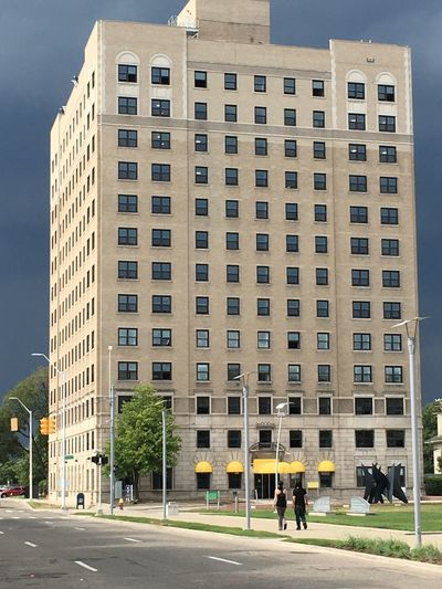 Architecture Building Exterior Built Structure City Day Outdoors Travel Destinations Skyscraper Sky People Adult Walking Dark Sky Detroitlove Streetphotography Stoplight Detroit Buildings DetroitMichigan Two People People Watching People Walking  The Week On EyeEm EyeEmNewHere