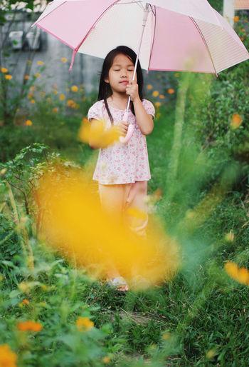 Full length of happy girl holding umbrella